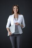 Young woman holding a laptop, isolated on grey. Portrait of young woman holding a laptop, isolated on grey background royalty free stock images