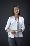 Young woman holding a laptop, isolated on grey. Portrait of young woman holding a laptop, isolated on grey background royalty free stock image