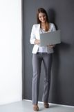 Young woman holding a laptop, isolated on grey Royalty Free Stock Photos