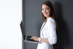 Young woman holding a laptop, isolated on grey Royalty Free Stock Image
