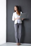 Young woman holding a laptop, isolated on grey Royalty Free Stock Photography