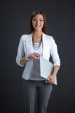 Young woman holding a laptop, isolated on grey. Portrait of young woman holding a laptop, isolated on grey background royalty free stock photo