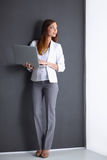 Young woman holding a laptop, isolated on grey. Portrait of young woman holding a laptop, isolated on grey background stock photos