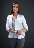 Young woman holding a laptop, isolated on grey Royalty Free Stock Photo