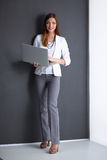 Young woman holding a laptop, isolated on grey. Portrait of young woman holding a laptop, isolated on grey background royalty free stock photos