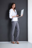 Young woman holding a laptop, isolated on grey Stock Images