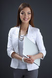 Young woman holding a laptop, isolated on grey Stock Photos