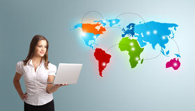Young woman holding a laptop and presenting colorful world map Royalty Free Stock Photo