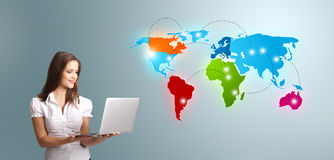 Young woman holding a laptop and presenting colorful world map Royalty Free Stock Images