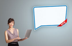 Young woman holding a laptop and presenting modern speech bubble. Beautiful young woman holding a laptop and presenting modern speech bubble copy space stock photos