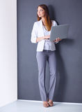 Young woman holding a laptop, standing on gray Royalty Free Stock Image
