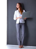 Young woman holding a laptop, standing on gray Stock Photo