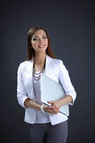 Young woman holding a laptop, standing on gray Royalty Free Stock Photos
