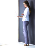 Young woman holding a laptop, standing on gray Stock Photography