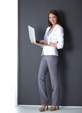 Young woman holding a laptop, standing on gray Stock Images