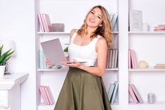 Young woman holding laptop, working on computer or student studying. Casual blogger woman with laptop, working at home. Female business. Blonde business woman royalty free stock images