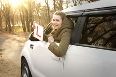 Young woman holding learner driver sign wh. Ile looking out of car window royalty free stock image