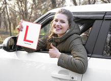 Young woman holding learner driver sign while looking. Out of car window Royalty Free Stock Image