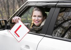 Young woman holding learner driver sign. While looking out of car window Stock Photos