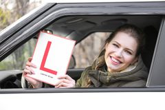 Young woman holding learner driver sign. While looking out of car window Royalty Free Stock Photo