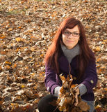 Young woman holding leaves. Young womanholding big autumn orange leaves stock photography