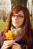 Young woman holding leaves. Young womanholding big autumn orange leaves royalty free stock photos
