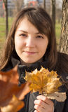 Young woman holding leaves. Young womanholding big autumn orange leaves stock images