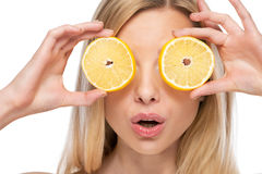 Young woman holding lemon slices in front of eyes Royalty Free Stock Image