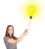 Young woman holding a light bulb balloon Stock Photos