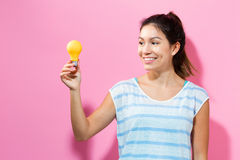 Young woman holding a light bulb Royalty Free Stock Photography