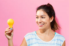 Young woman holding a light bulb Royalty Free Stock Photos