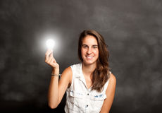 Young woman holding a lightbulb Royalty Free Stock Photography