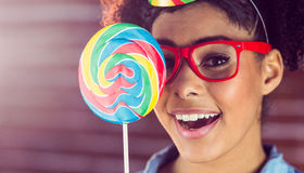 Young woman holding a lollipop against her face Royalty Free Stock Photo