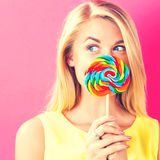 Young woman holding a lollipop. On a pink background Royalty Free Stock Photos