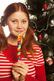 young woman  holding lolly pop. Christmas tree. Royalty Free Stock Photography