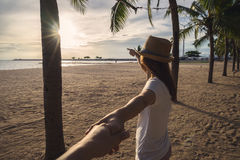Young woman holding man`s hand on the beach royalty free stock photo