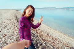 Young woman holding man's hand and showing peace sign Stock Photos