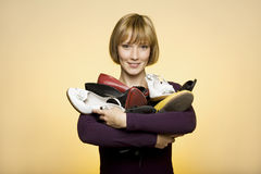 Young woman holding many shoes Royalty Free Stock Photography