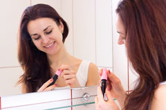 Young woman holding mascara in bathroom Stock Image