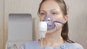 Young woman holding a mask from an inhaler at home. Treats inflammation of the airways via nebulizer. Preventing asthma stock footage