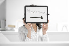 Young Woman Holding 'Meeting' Sign Royalty Free Stock Photo