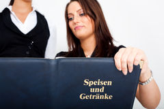 A young woman holding a menu card and a waitress. A young woman in a restaurant, holding a menu card in her hands Stock Image