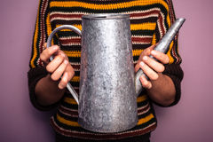 Young woman holding metal watering can Stock Photo