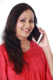 Young woman holding mobile phone against white Stock Photography