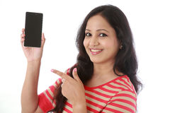 Young woman holding mobile phone against white Stock Images