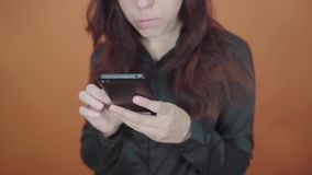 Young woman holding mobile phone in hand on orange background. Female typing a message on a smartphone. Young female holding mobile phone in hand on orange stock video footage