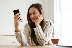 Young woman holding mobile phone and looking at text message. Portrait of young woman holding mobile phone and looking at text message Stock Photography