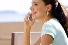 Young woman holding mobile phone outdoors, smiling, side view, close-up Royalty Free Stock Image