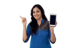 Young woman holding mobile phone and showing copy space Royalty Free Stock Photography