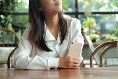 Young woman holding mobile phone thinking and waiting for someon. Young asia woman holding mobile phone thinking and waiting for someone in coffee cafe. image Stock Image